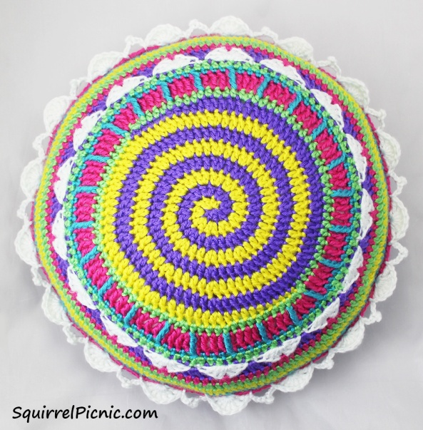 """This 14"""" round pillow is as fun to make as it looks! Every round takes you on an adventure. For an even brighter pillow make yours with Caron Simply Soft."""